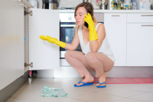 Lady looking under her sink at frustrating plumbing repair.